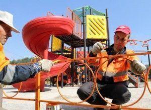 В рамках программы по благоустройству ограждения детской площадки красят в новый яркий цвет