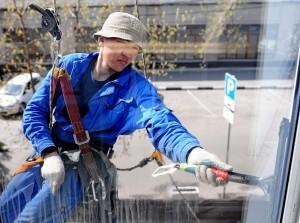 Промышленный альпинист Мухтар Хаджиматов моет окна здания в Бумажном проезде