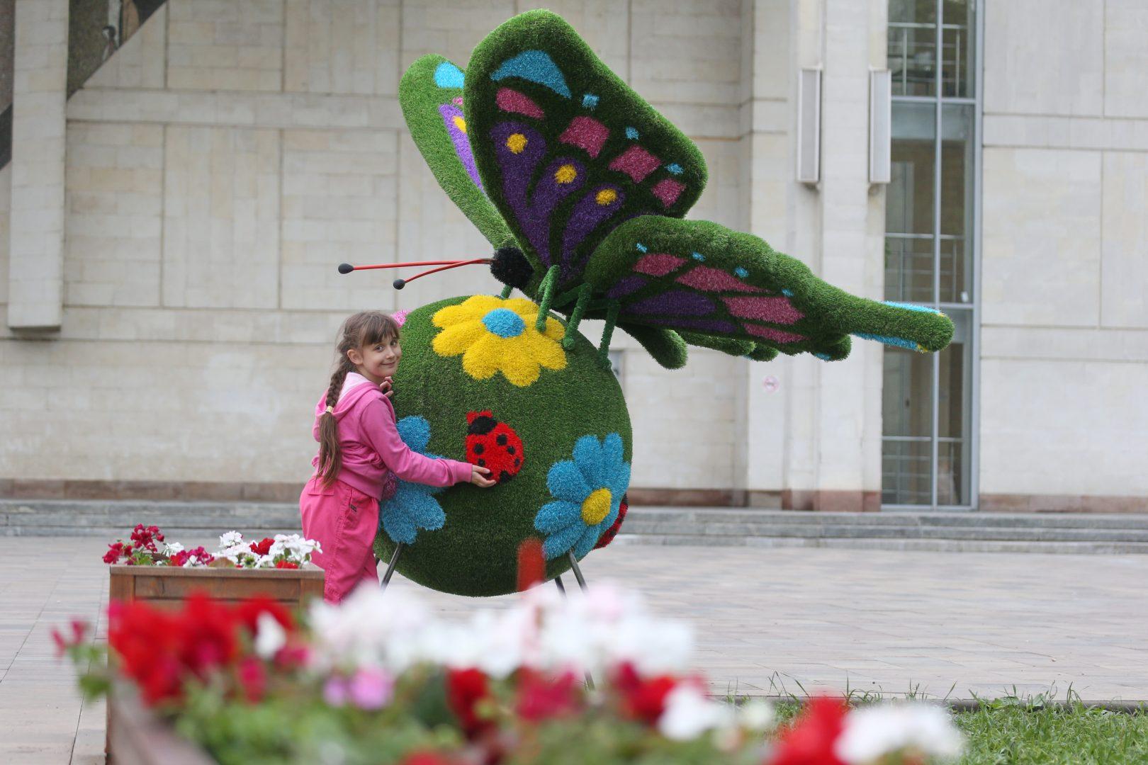 20 мая 2018 года. Московский. Наташа Кузнецова радуется яркой бабочке, что «прилетела» на центральную площадь поселения. Фото: Виктор Хабаров